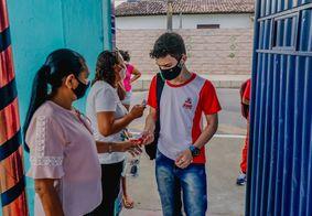 Estudantes passam por higienização em retomada às aulas presenciais.