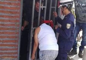 Mulher tenta bisbilhotar vizinha e acaba com cabeça presa em portão