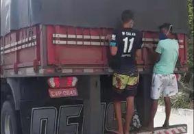 Jovens são flagrados 'pegando carona' na traseira de caminhão
