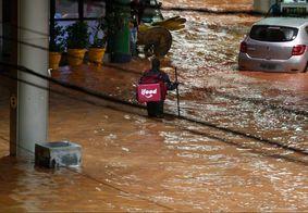 Foto de entregador tentando atravessar rua alagada viraliza na web e levanta debate; veja
